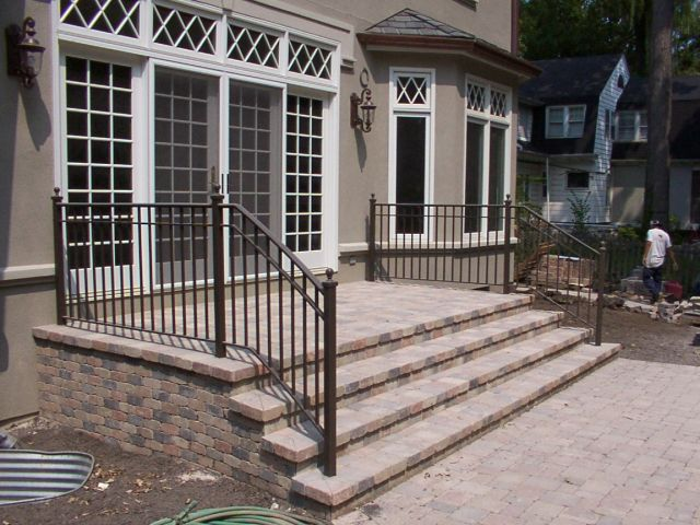 """Colonial"" style railing. Curved to follow flair of steps. Bronzetone finish.  2 in. newel posts with cast iron ball cap finials."